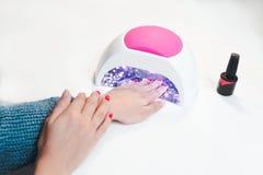 Kvinnahanden inom UV lampan för spikar på tabellslut upp royaltyfri foto