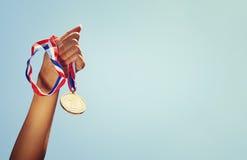 Kvinnahanden lyftte och att rymma guldmedaljen mot himmel utmärkelse- och segerbegrepp Royaltyfri Bild