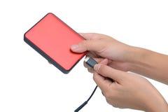 Kvinnahanden satte USB kabel in i den isolerade yttre hårddisken på whi Arkivfoto