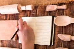 Kvinnahanden skriver ett recept i kokbok Boka för recept runt om redskap på träbakgrund Royaltyfria Foton