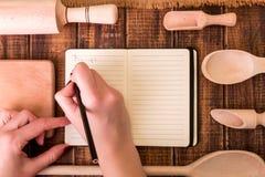 Kvinnahanden skriver ett recept i kokbok Boka för recept runt om redskap på träbakgrund Royaltyfria Bilder