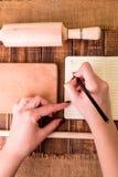 Kvinnahanden skriver ett recept i kokbok Boka för recept runt om redskap på träbakgrund Royaltyfri Fotografi