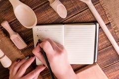 Kvinnahanden skriver ett recept i kokbok Boka för recept runt om redskap på träbakgrund Fotografering för Bildbyråer