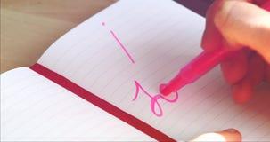 Kvinnahanden skriver på anteckningsbokorden som JAG ÄLSKAR DIG
