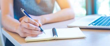 Kvinnahanden skriver på notepaden med pennan i regeringsställning arkivbild