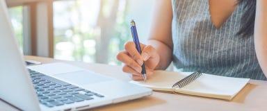 Kvinnahanden skriver på notepaden med pennan i regeringsställning royaltyfri bild