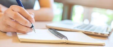 Kvinnahanden skriver på notepaden med pennan i regeringsställning arkivfoton