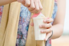 Kvinnahanden som öppnar sojabönorna för fruktsallad, mjölkar gelé, yoghurten, efterrätten, sunt, sött som är smaskig Arkivfoton