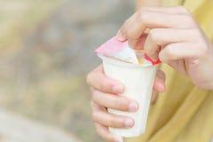 Kvinnahanden som öppnar sojabönorna för fruktsallad, mjölkar gelé, yoghurten, efterrätten, sunt, sött som är smaskig Fotografering för Bildbyråer