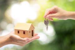 Kvinnahanden som rymmer ett modellhem och en tangent som köper ett nytt hus, lurar arkivbild