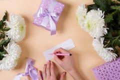 Kvinnahanden som skriver en anmärkning med texten, tackar dig på en pape Fotografering för Bildbyråer