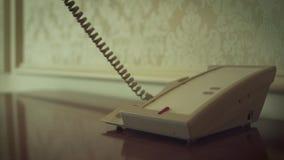 Kvinnahanden som tar telefonen, handset för att kalla i hotellrum lager videofilmer