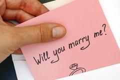 Kvinnahanden som ut tar brevet med text, ska du att gifta sig mig? från e Arkivfoton