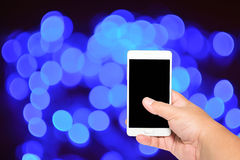 Kvinnahandhåll och smart telefon för pekskärm på bokehbakgrund Arkivfoton