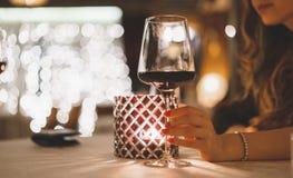 Kvinnahandhåll per exponeringsglas av vin i en restaurang med aftonstearinljusbelysning Royaltyfria Bilder