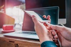 Kvinnahandhållen den laddande kabeln som pluggar den smarta mobiltelefonen, matten och oväsenfiltret applicerar Royaltyfri Bild