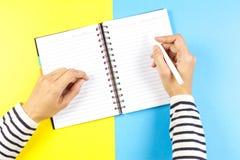 Kvinnahandhandstil i anteckningsbok över blått- och gulingbakgrund Top beskådar Arkivfoton