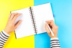 Kvinnahandhandstil i anteckningsbok över blått- och gulingbakgrund Top beskådar Arkivbilder