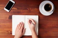 Kvinnahandhandstil i en dagbok royaltyfri foto