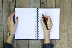 Kvinnahandhandstil på anteckningsboken med pennan royaltyfri fotografi