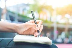 Kvinnahandhandstil på en notepad med en penna Royaltyfri Foto