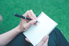 Kvinnahandhandstil på en notepad med en penna Royaltyfri Bild