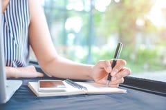 Kvinnahandhandstil på notepaden med en penna i kontoret Fotografering för Bildbyråer