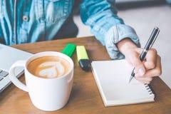 Kvinnahandhandstil på notepaden med en penna i regeringsställning Arkivfoton
