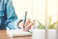 Kvinnahandhandstil på notepaden med en penna i regeringsställning Royaltyfria Foton