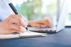 Kvinnahandhandstil på notepaden med en penna och arbeten i en bärbar dator c Arkivbilder