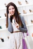 Kvinnahandkreditkorten i skodon shoppar Royaltyfri Foto