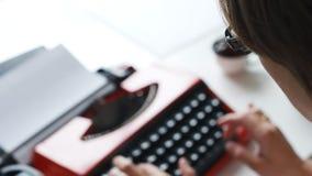 Kvinnahandmaskinskrivning på den röda tappningskrivmaskinen arkivfilmer