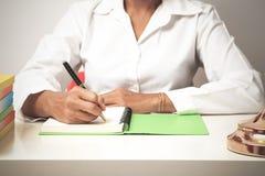 Kvinnahandstil i den spiral notepaden som förläggas på det ljusa skrivbordet med th Royaltyfri Foto