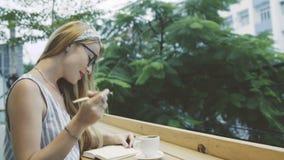 Kvinnahandstil i hennes tidskrift, dagbok Den emotionella kvinnlign skriver i anteckningsbok och drickakaffe i kafé lager videofilmer