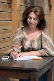 Kvinnahandstil något till anteckningsboken genom att använda pennan Royaltyfria Foton