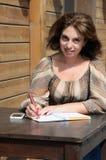 Kvinnahandstil något till anteckningsboken genom att använda pennan Arkivfoton
