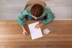 Kvinnahandstil på arket av papper på tabellen inomhus arkivbild