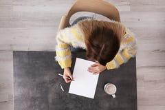 Kvinnahandstil på arket av papper på tabellen inomhus royaltyfri fotografi