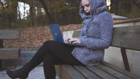 Kvinnahandstil på bärbara datorn parkerar på bänken stock video