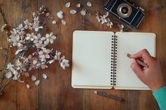 Kvinnahandstil på den tomma anteckningsboken bredvid trädet för körsbärsröda blomningar för vår det vita på tappningträtabellen Arkivbild