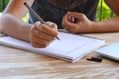 Kvinnahandstil på en notepad, närbild av pennan i hand arkivbilder