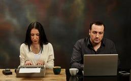 Kvinnahandstil på en skrivmaskin och en man som arbetar på en bärbar dator teched fotografering för bildbyråer