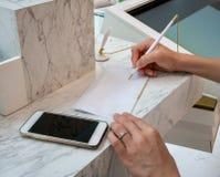 Kvinnahandstil på ett vitt ark av papper Si för hand för affärskvinna fotografering för bildbyråer