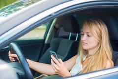 Kvinnahandstilsms, medan köra bilen Fotografering för Bildbyråer