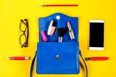 Kvinnahandväska, skönhetsprodukter, smartphone, exponeringsglas på en ljus gul bakgrund, bästa sikt Royaltyfri Fotografi