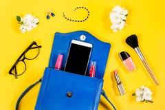 Kvinnahandväska, skönhetsprodukter, smartphone, exponeringsglas på en ljus gul bakgrund, bästa sikt Arkivfoto
