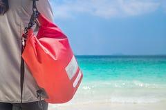 KvinnaHang Dry PackWaterproof bagage på stranden Arkivbilder