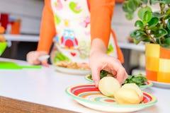 Kvinnahastiga greppet skalade potatisen förbi handen, i modernt kök royaltyfri fotografi