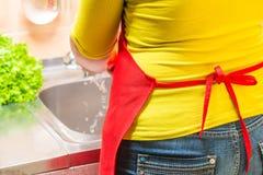 kvinnahemmafrun tvättar grönsaker i köket royaltyfri fotografi