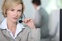 Kvinnaholdinghörlurar med mikrofon. Royaltyfri Foto